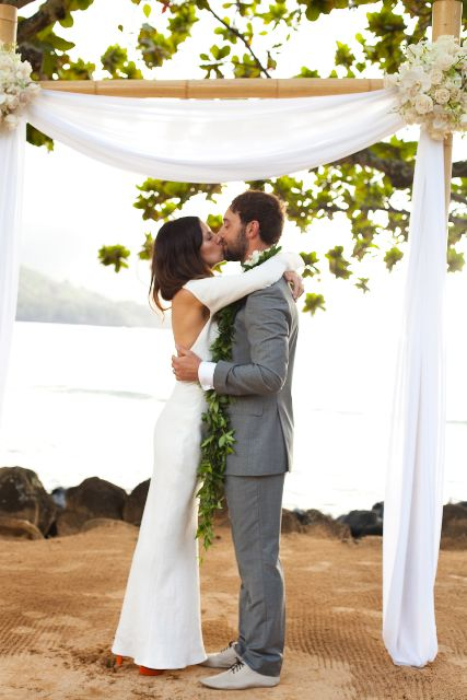 a bamboo wedding arbor decorated with white flowy curtains, with neutral blooms is a timeless idea