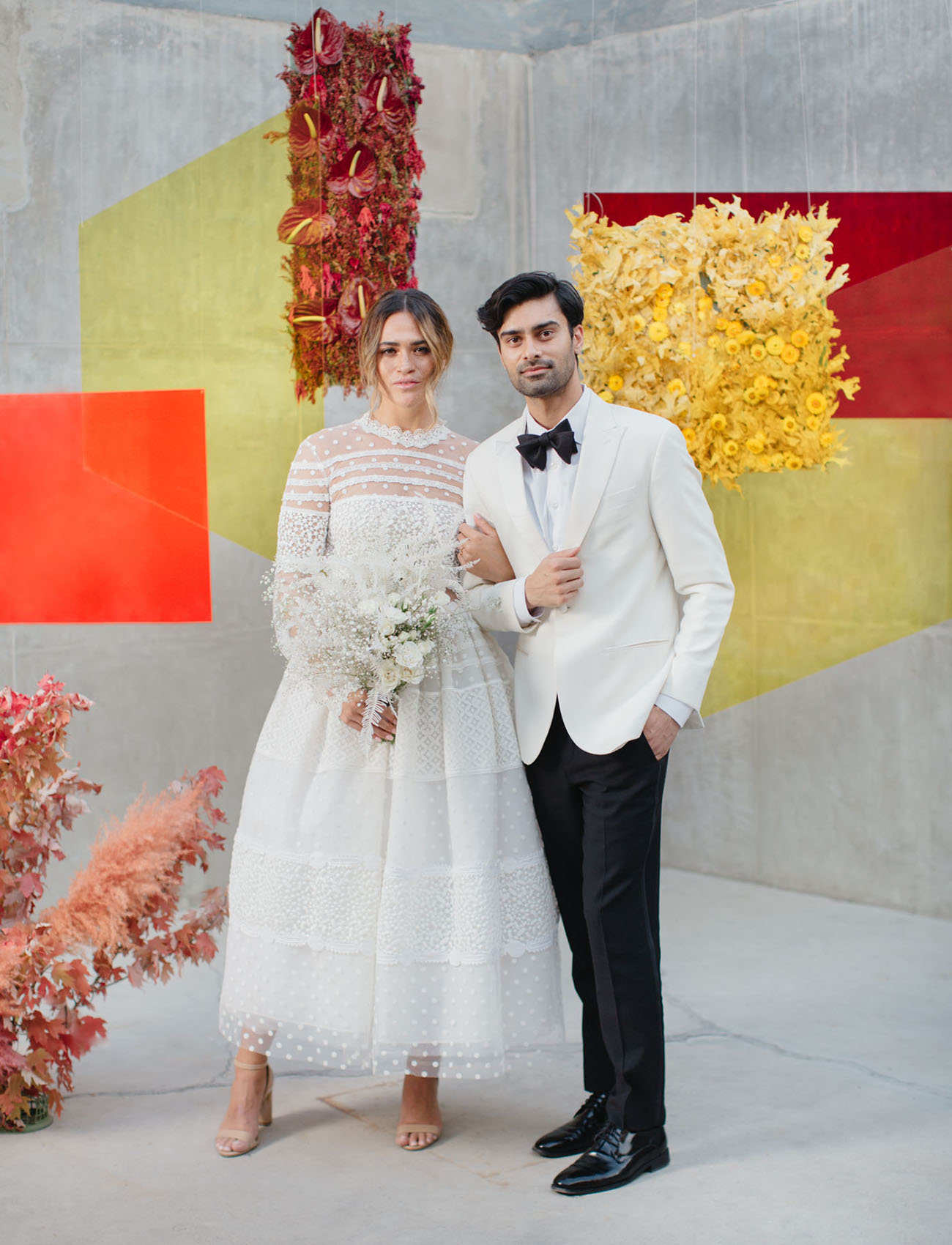 a color block wedding backdrop with burgundy, yellow and red figures and floral installations