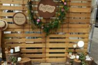 19 a rustic photo booth backdrop of pallets, with stumps and wood slices, candles and a floral wreath
