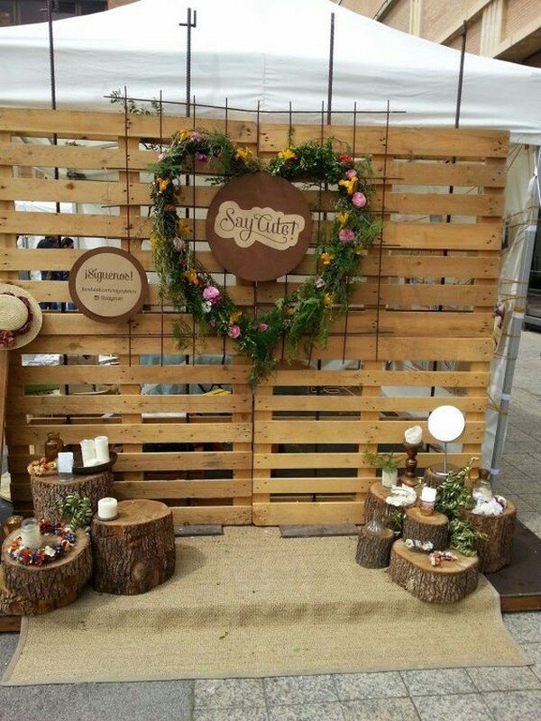 a rustic photo booth backdrop of pallets, with stumps and wood slices, candles and a floral wreath