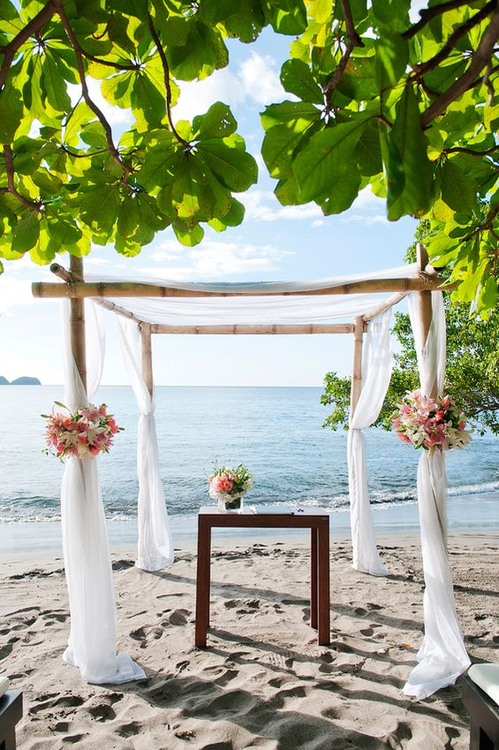 a bamboo wedding arbor styled with white curtains and white nd pink blooms right on the beach