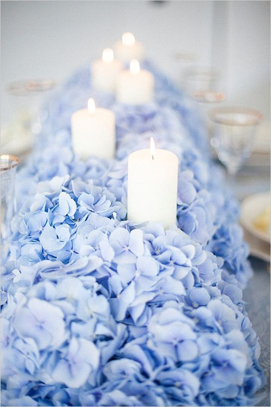 a jaw-dropping blue hydrangea wedding table runner with candles is a cool centerpiece substitution