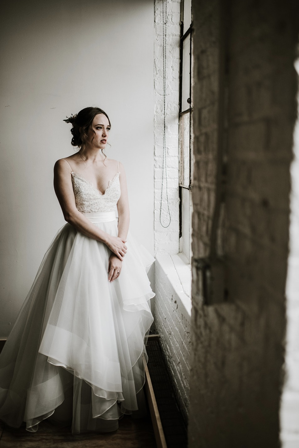 a romantic wedding ballgown with a lace bodice and spaghetti straps and a layered high low skirt