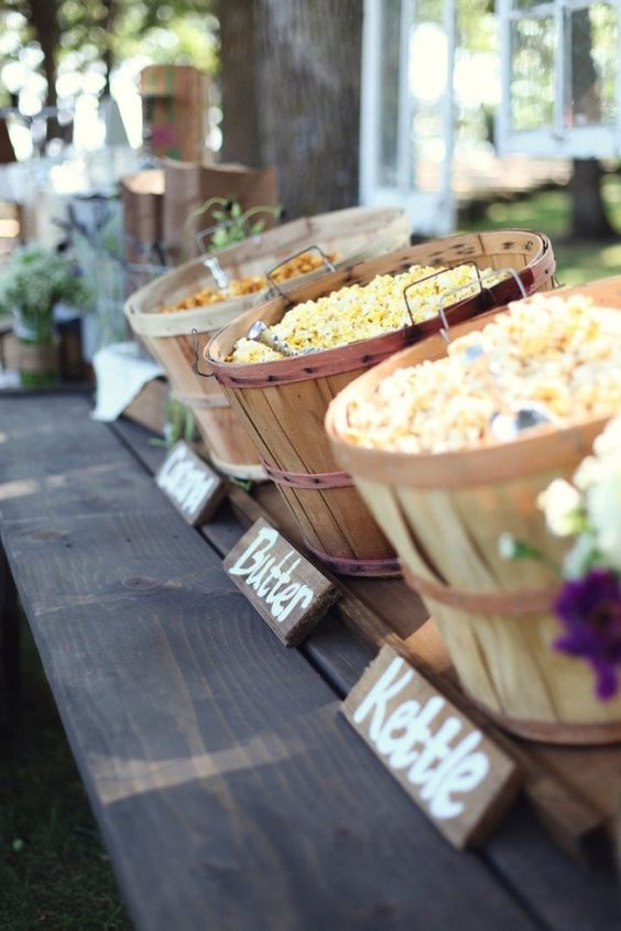 a rustic popcorn bar done with wooden baskets and wooden signs is a very cozy idea