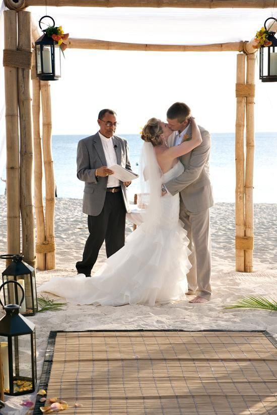 a bamboo wedding arbor with lanterns hanging on it and lanterns around it is amazing for tropical weddings