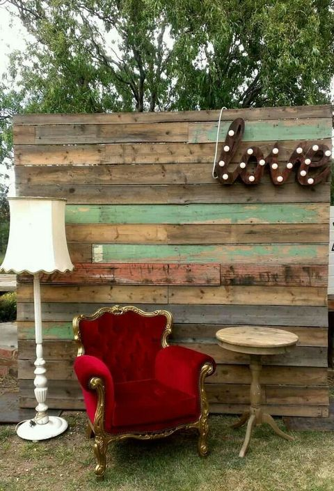 a shabby chic photo booth backdrop of weathered wood, a LOVE marquee, a vintage red chair and lamps