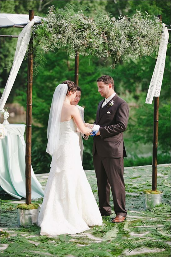 a bamboo wedding chuppah  placed into buckets with moss and decorated with little blooms and greenery