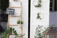 22 a simple photo booth with a boho twist, lanterns, greenery, greenery wreaths and a couple of doors