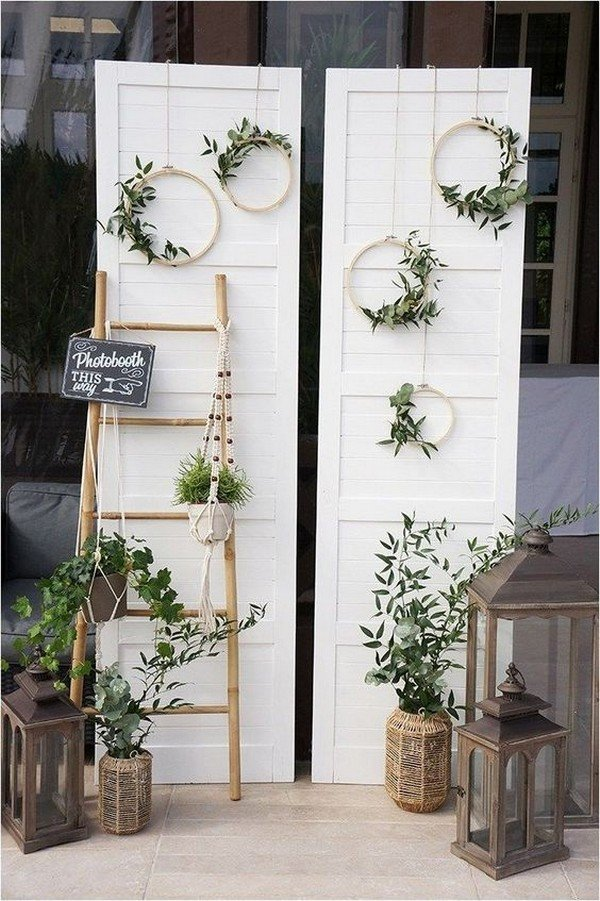 a simple photo booth with a boho twist, lanterns, greenery, greenery wreaths and a couple of doors