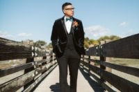 22 a velour jacket tux, a blue bow tie, a bold boutonniere and black embroidered velvet loafers for a dashign touch