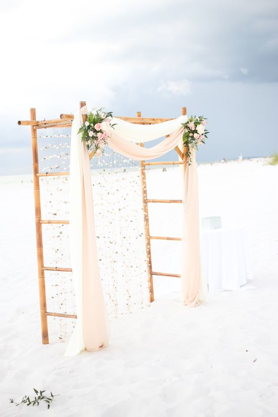 a cool bamboo wedding arbor with flowy fabric, blush and white blooms, greenery and rhinestones hanging down