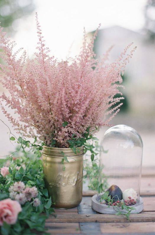 a simple wedding bouquet of a gold jar with pink flowers is a chic and bold decor idea