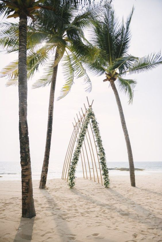 a creative beach wedding ceremony arbor saped as a boat and decorated as greenery and white blooms
