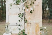 24 a vintage travel-inspired backdrop of two shabby chic doors, greneery, buntings, a stack of suitcases and a stool with blooms