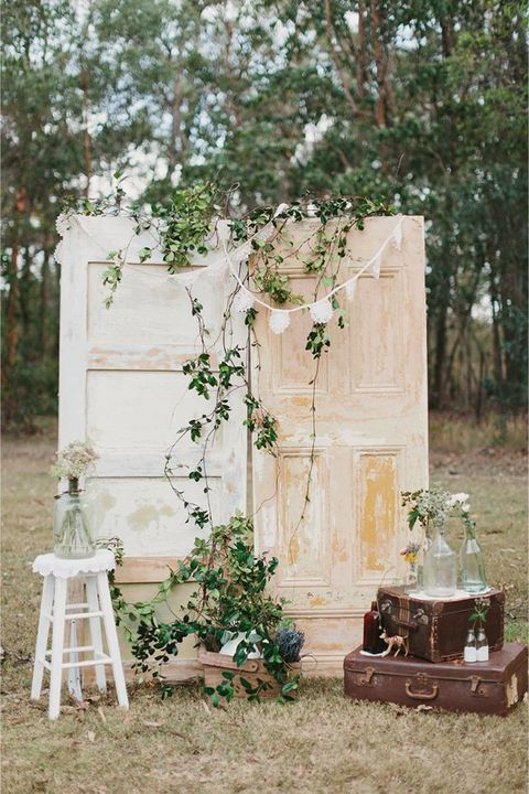 a vintage travel-inspired backdrop of two shabby chic doors, greneery, buntings, a stack of suitcases and a stool with blooms