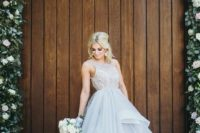 24 a whimsy wedding ballgown with a lace sleeveless bodice with a high neckline and a grey layered full skirt with a train