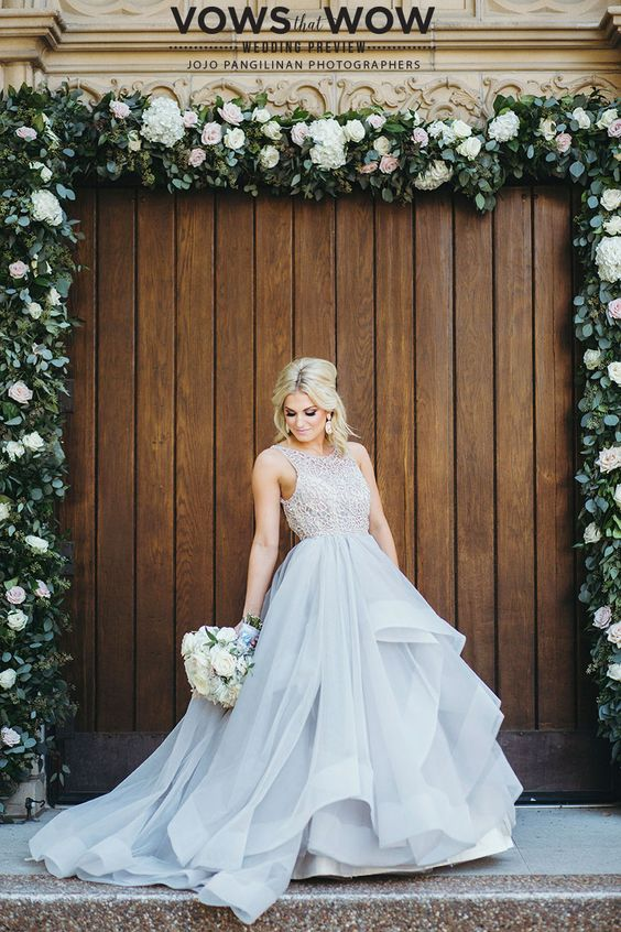 a whimsy wedding ballgown with a lace sleeveless bodice with a high neckline and a grey layered full skirt with a train