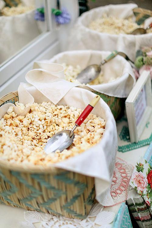 a simple and cozzy popcorn bar with wicker baskets and neutral fabric and various kinds of popcorn