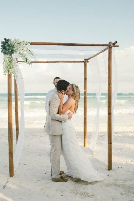 a tropical wedding arbor of bamboo with flowy white fabric, greenery and white blooms on one corner