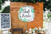 25 a vintage wedding photo booth with greenery topiaries, a paper decoration, lanterns and signs