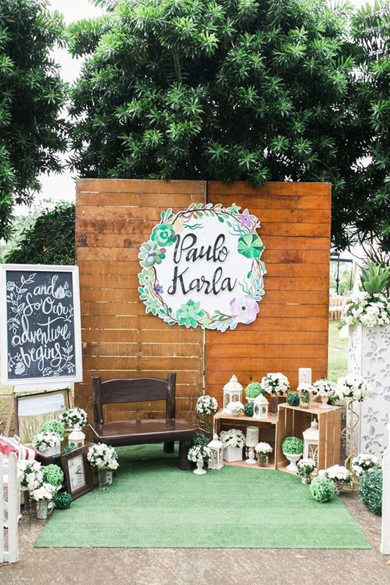 a vintage wedding photo booth with greenery topiaries, a paper decoration, lanterns and signs