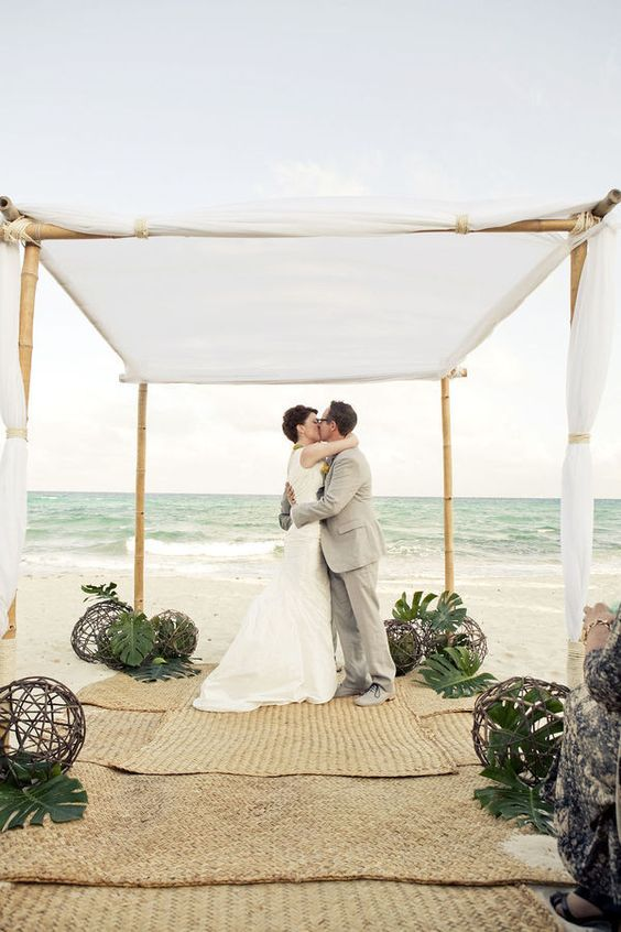 a wedding chuppah of bamboo topped with white fabric, tropical leaves and wicker balls on the floor