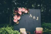 26 an elegant photo booth with a black and monogram backdrop decorated with paper flowers and refiend chairs