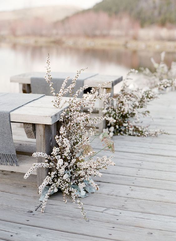 neutral blooms and pale foliage by the benches create a frozen winter wedding aisle
