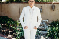 02 One bride chose a braided updo, a white suit with a necklace and nude shoes