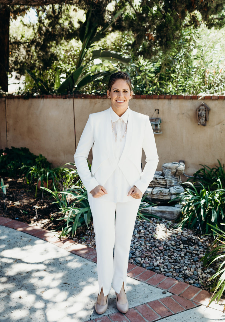 One bride chose a braided updo, a white suit with a necklace and nude shoes