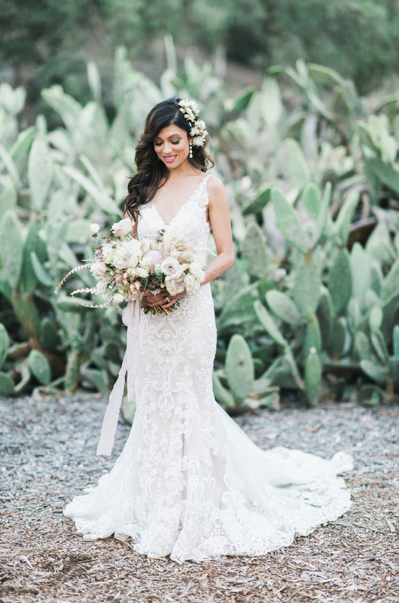 The bride was wearing a fantastic lace mermaid wedding dress with thin straps and a V-neckline plus fresh flowers in her hair