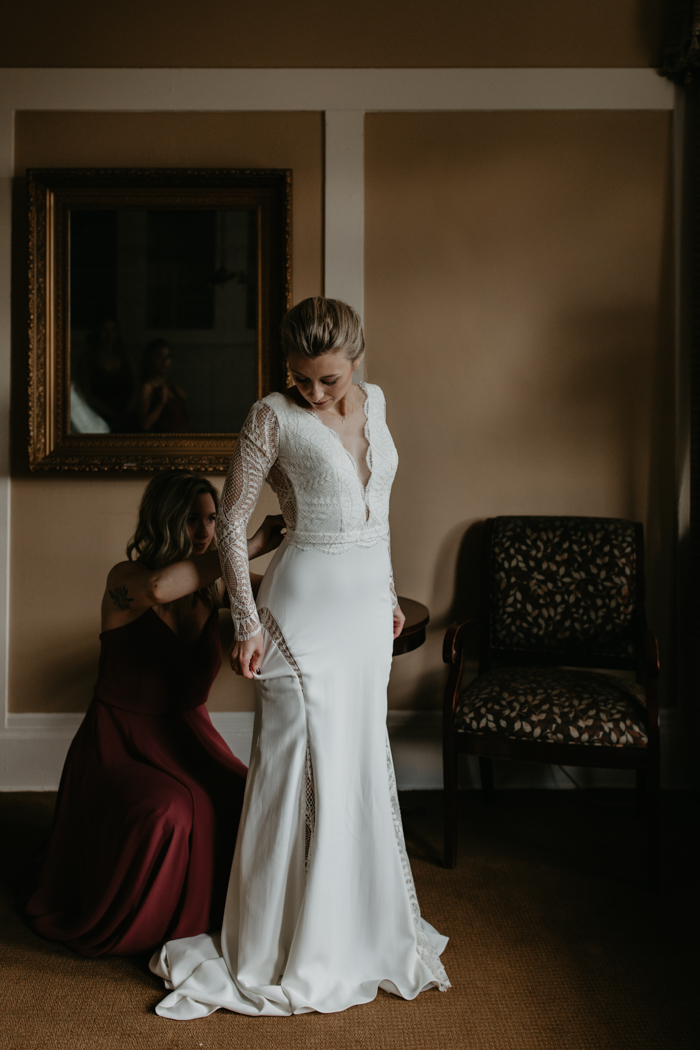 The bride was wearing a fitting wedding dress with a lace bodice and sleeves, with a plunging neckline, cutout back and lace inserts