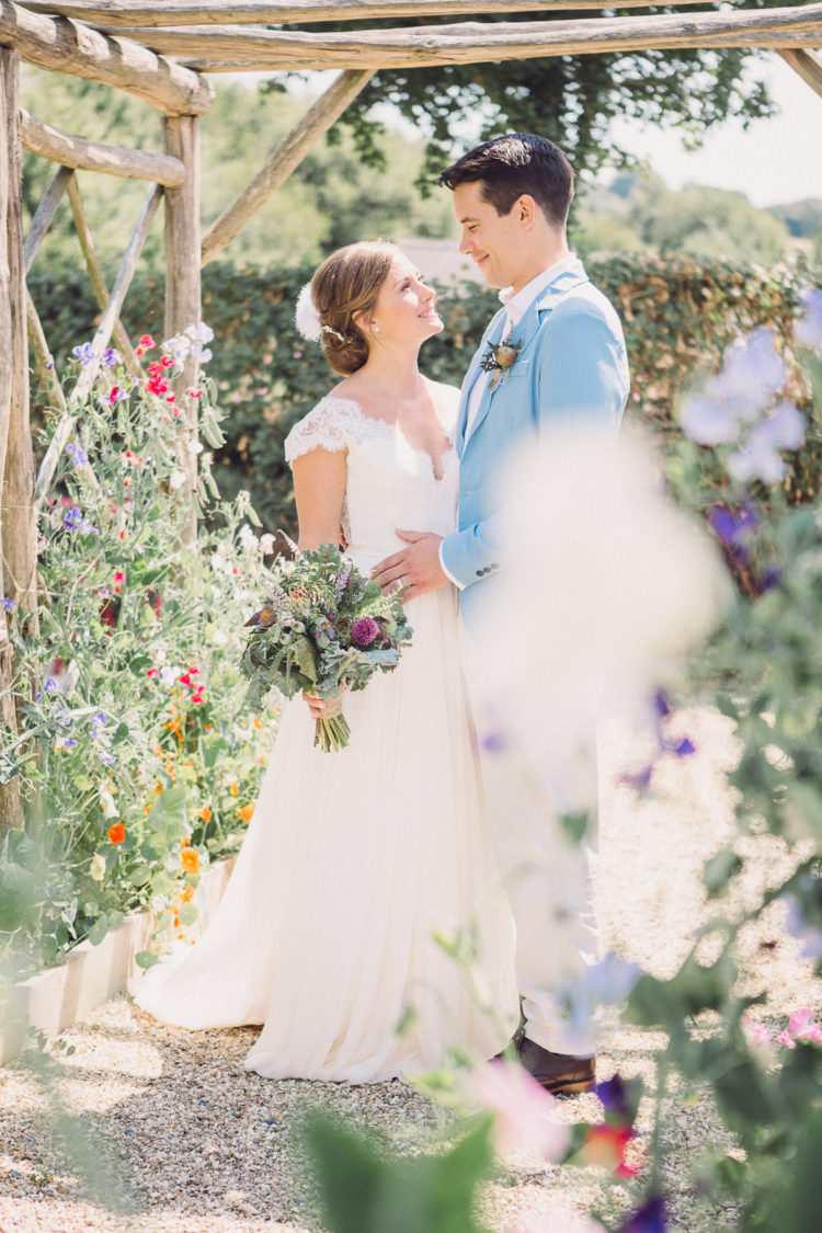 The bride was wearing a lace A-line wedding gown with a V-neckline, cap sleeves