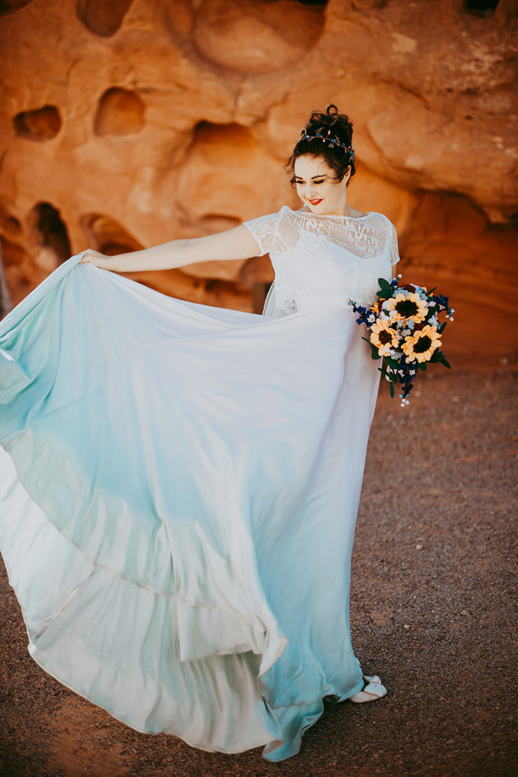 The bride was wearing an ombre white to turquoise wedding dress with a lace coverup, a teal headpiece