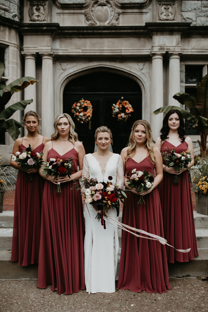 The bridesmaids were wearing burgundy maxi dresses on spaghetti straps
