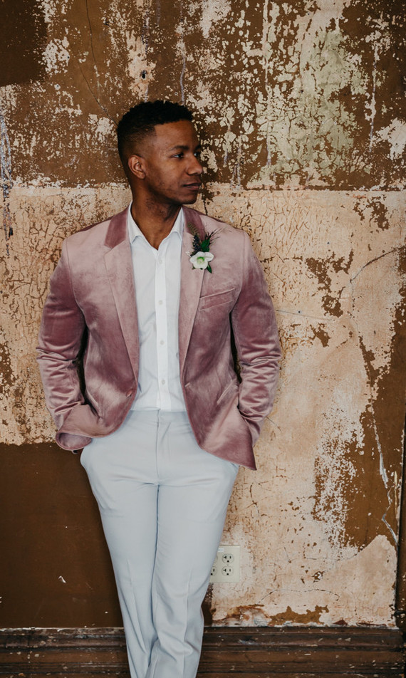 The groom was wearing a white shirt, off-white pants, a pink velvet blazer and Chelsea boots