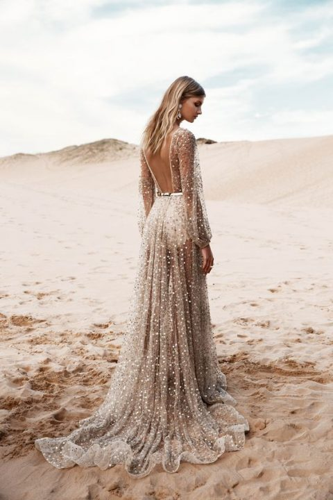 a fully embellished sheer wedding dress with a cutout back, long sleeves and a train