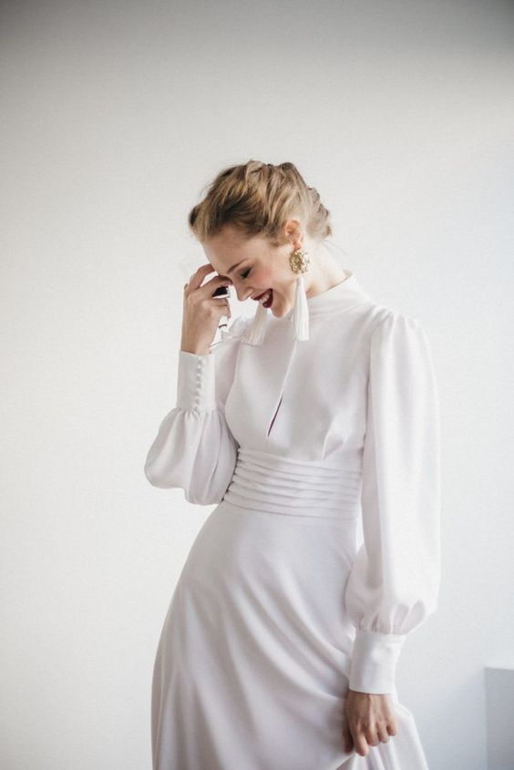 a modern take on a vintage wedding dress   a plain turtleneck Victorian inspired wedding gown with long sleeves and tassel earrings