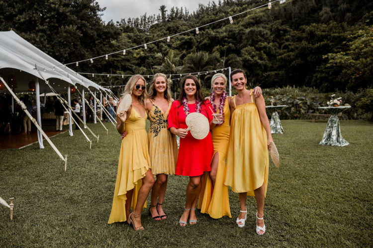 The bridesmaids were wearing mismatching yellow dresses and the maid of honor was rocking a red dress