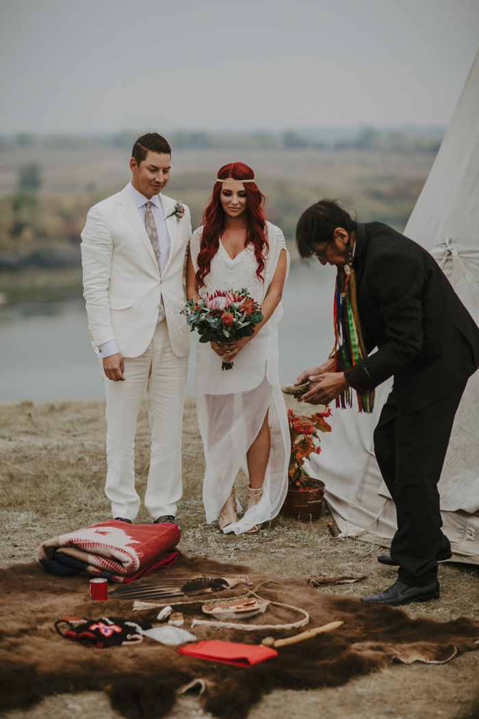 The groom was wearing an ivory suit with a white shirt and a printed tie, the bride was wearing a catchy modern wedding dress and embellished booties