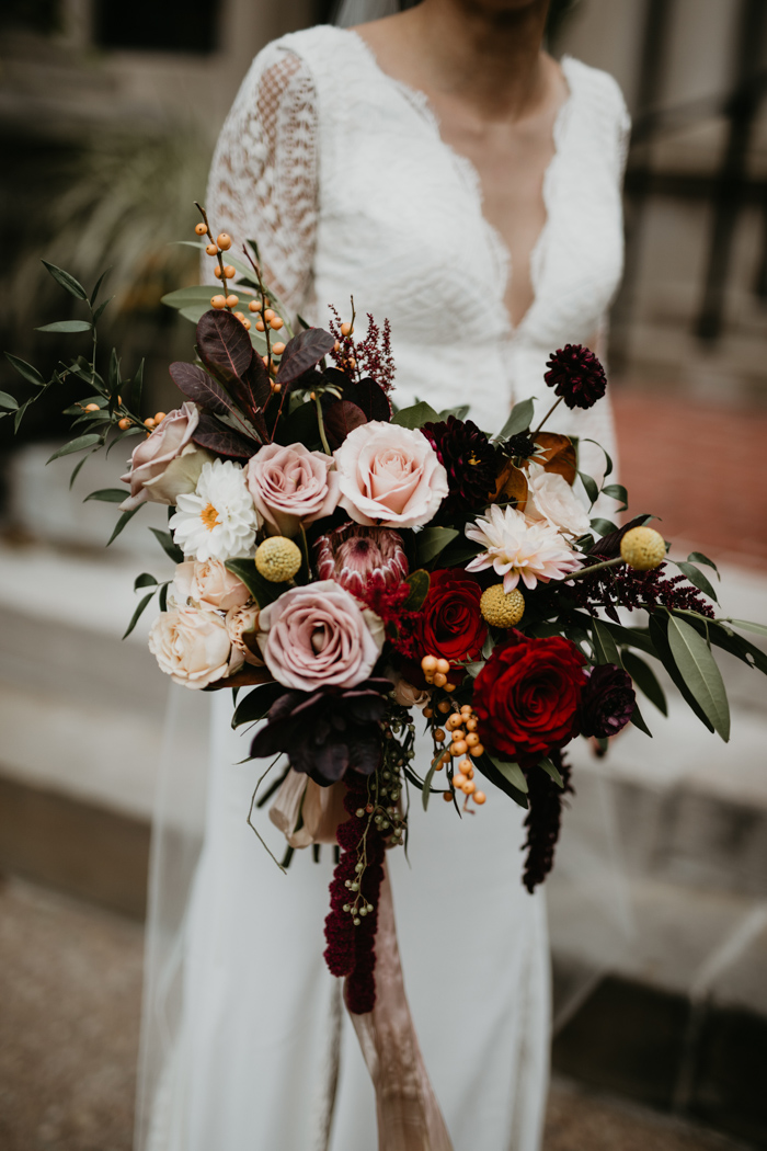 The wedding bouquet included red, blush, neutral blooms and green and dark foliage