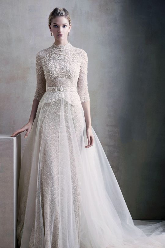 a beautiful vintage lace wedding dress with a turtleneck, half sleeves and an overskirt looks very delicate