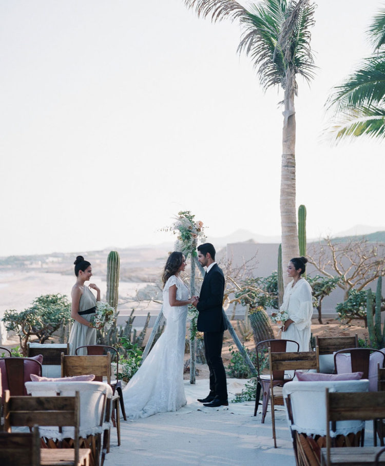 The ceremony space was a boho one, with mismatching chairs, a triangle arch, cacti and a gorgeous beach view