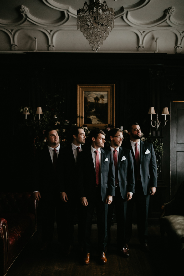 The groom and groomsmen were wearing black suits, burgundy ties and brown shoes