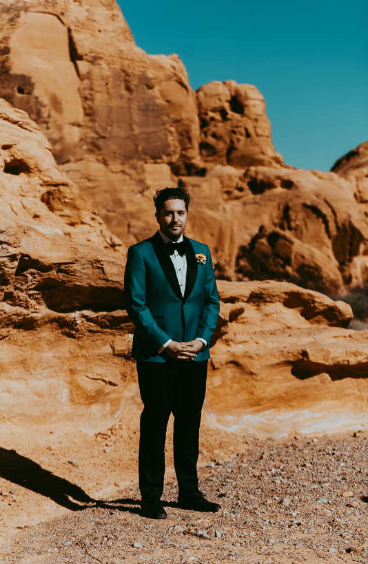 The groom was wearing a teal tuxedo with black lapels