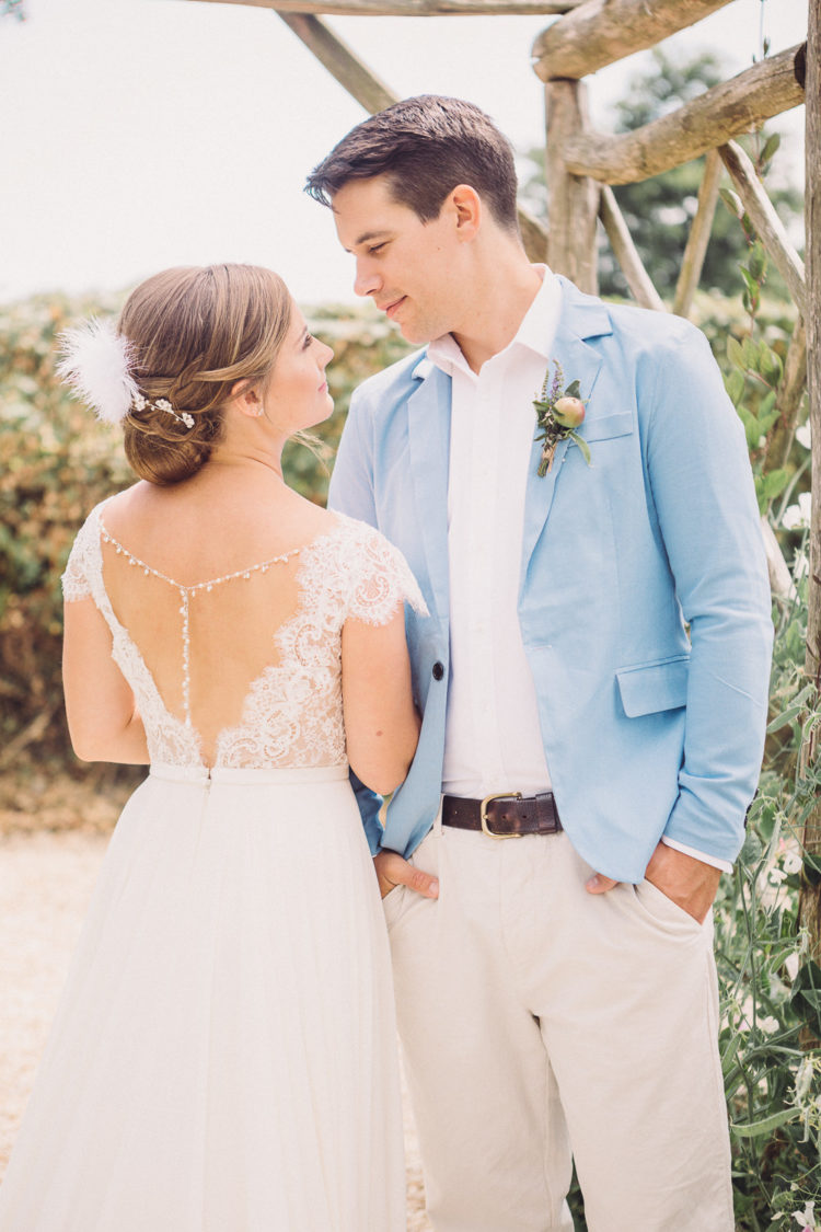The groom was wearing neutral pants, a white shirt and a light blue blazer
