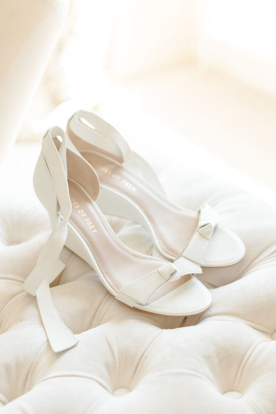 elegant and preppy white wedding wedges with little bows on top and thin platforms