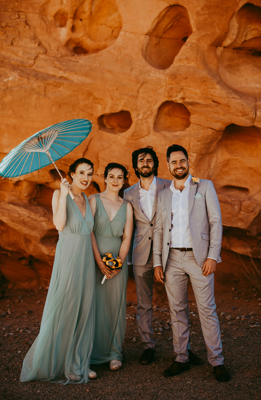 The bridesmaids were wearing aqu-colored maxi dresses with no sleeves and the groosmen were wearign greys
