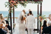 a bold tropical wedding arch in rustic style