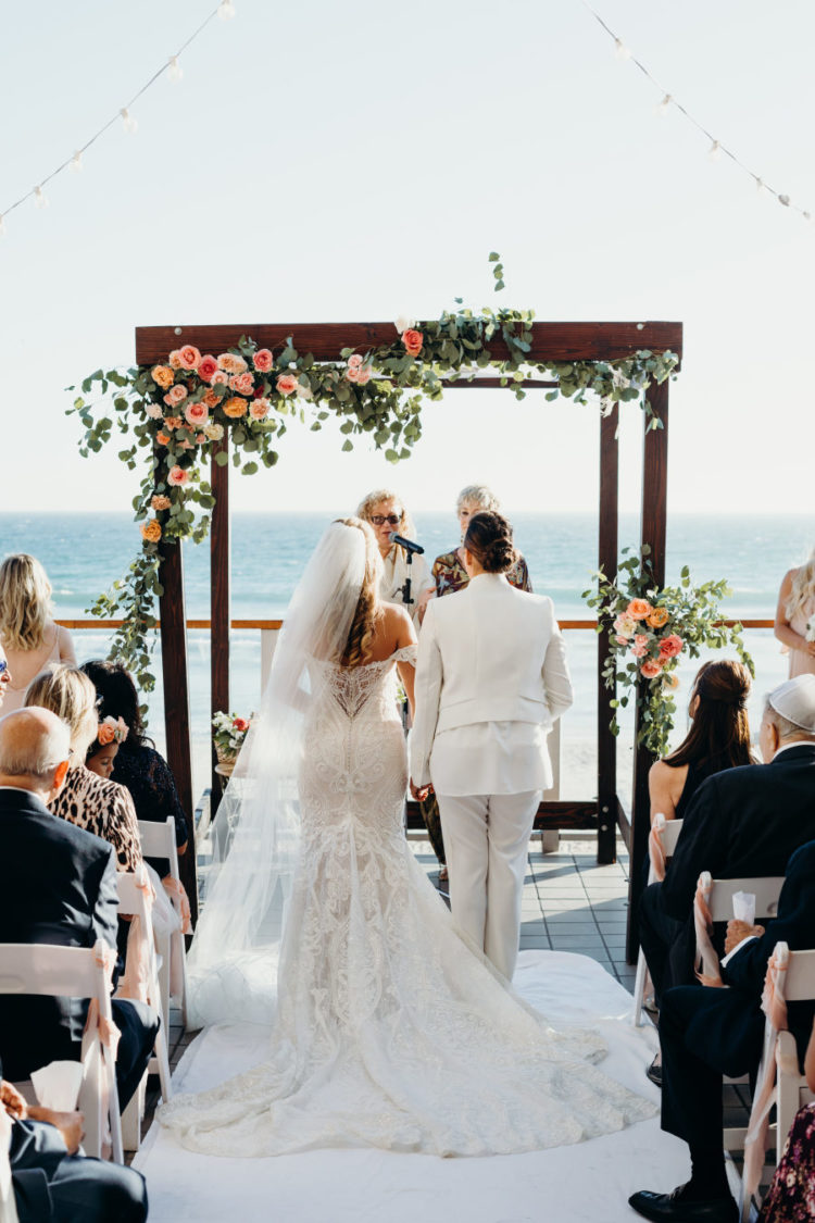 The wedding arch was a stained wooden one with lush blooms and greenery and with an ocean view